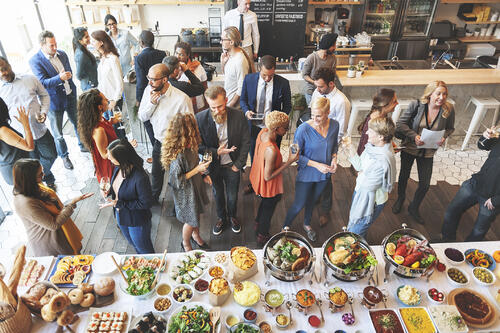 Attendees huddle around food and drinks at an event