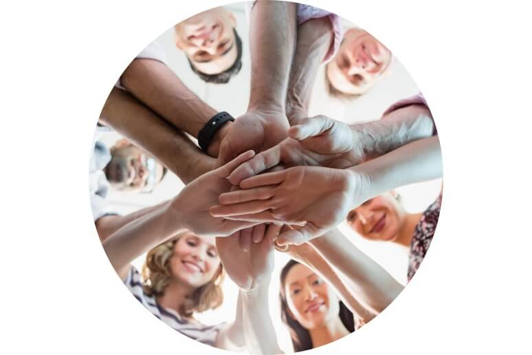 Group of people stacking hands in circle