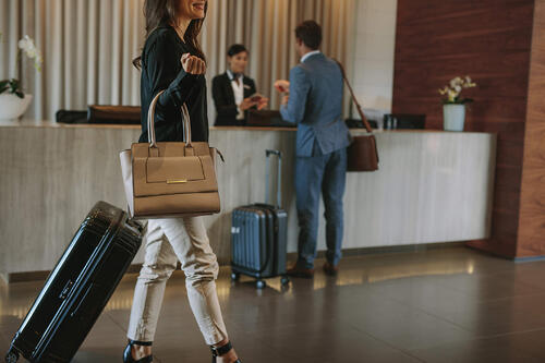 female business woman walking through hotel lobby with suitcases