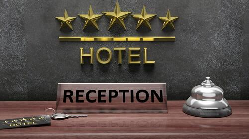 Reception sign placed on a desk with a key and bell at a hotel