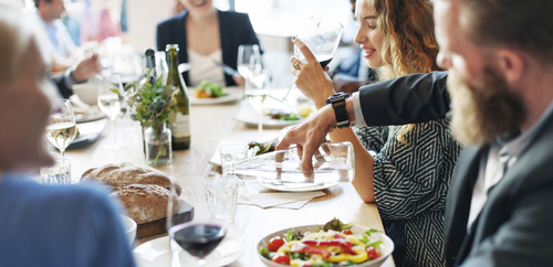 Business people networking, eating, and having a discussion during a hybrid event