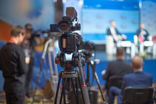camera pointed at stage where speakers host a hybrid event experience