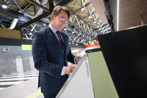 Male business professional using a self-service kiosk to check in at an event