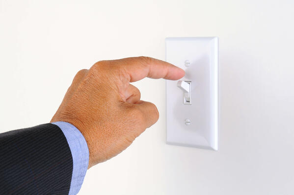 event sponsors hand with finger on light switch, about to turn off the lights