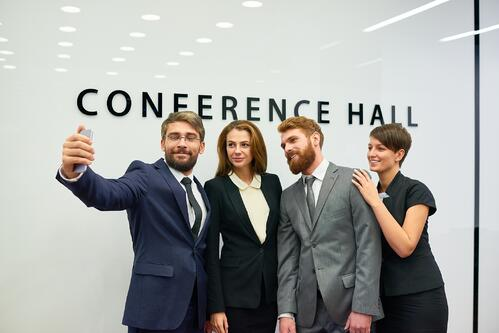 Event professionals taking a selfie together on a mobile phone