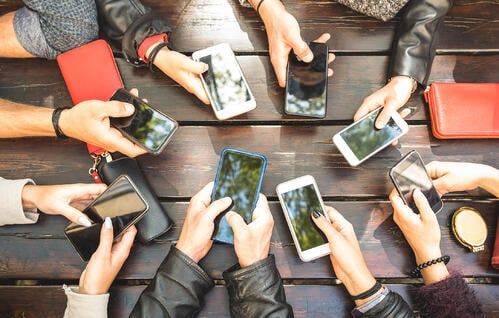 People sitting at a table in a circle holding their mobile phones using a networking app