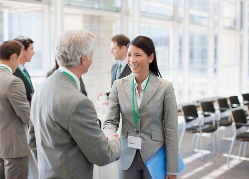 Male and female attendees shaking hands at a networking event