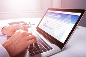 Male business professional using a laptop to register for an event online