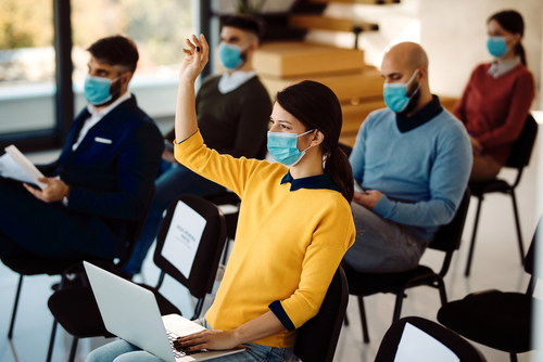 Female entrepreneur attending business seminar with her colleagues and raising her hand to ask a question. All of them are wearing face masks due to COVID-19 pandemic.