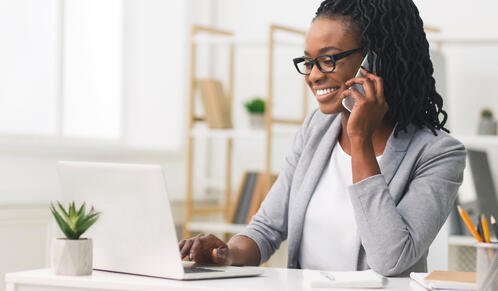 Businesswoman sitting at her desk talking on the phone
