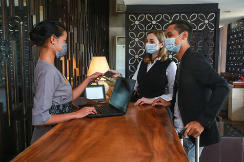 Businessman wearing a face mask checking into a hotel