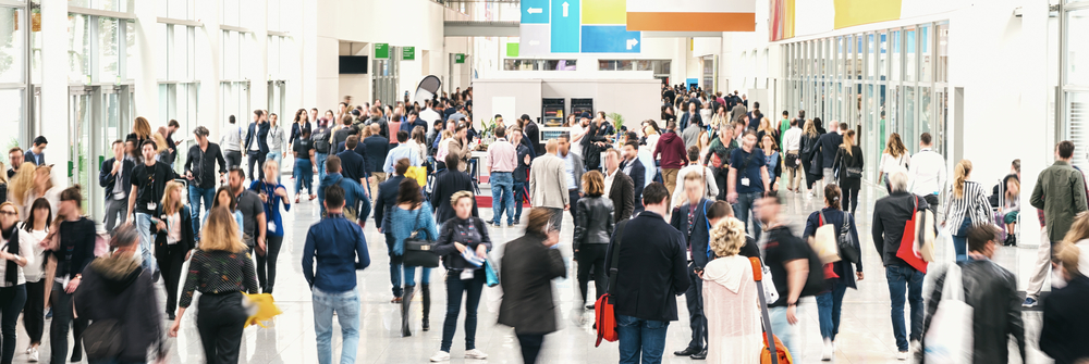 Attendees walking through the exhibition hall of an event
