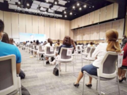 attendees practicing social distancing event by sitting 6 feet apart during an in-person event