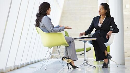 two business women having a 1 on 1 meeting at a conference table