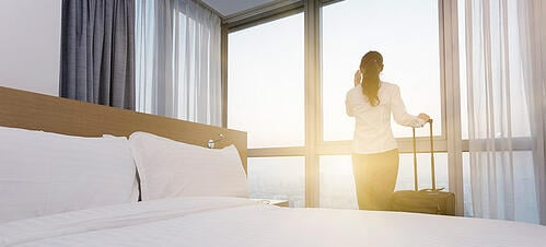 Businesswoman staring out the window of her hotel window