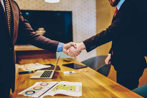 event professional shaking hands after negotiating a sponsorship agreement.
