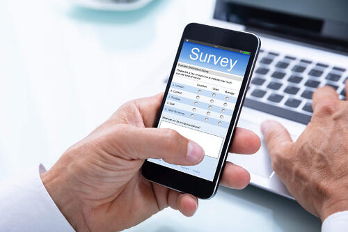 Businessman filling out a survey on his mobile event app