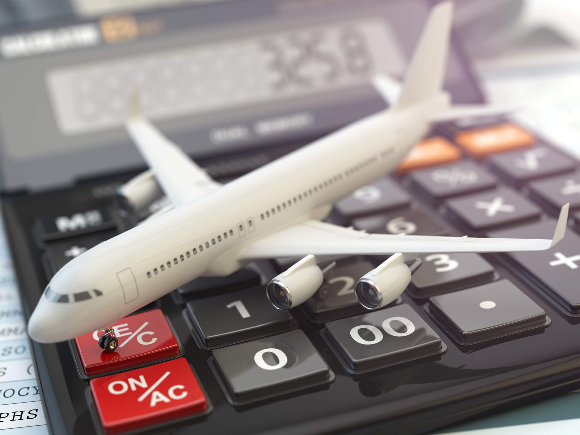 Miniature airplane laying across a calculator to symbolize travel management