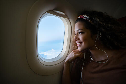 Female staring out the window while flying on a airplane