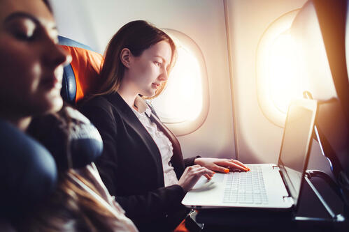 Businesswoman sitting on an airplane working on her laptop
