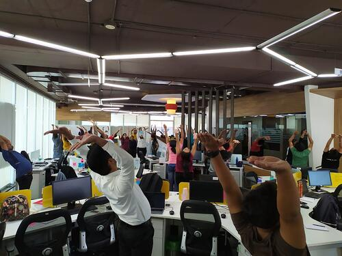 Aventri employees participating in yoga stretches while at their desks